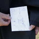 Father Cassian holds up a drawing by Andrei Diachkov of a possible tower for the bells. First the monks will have to generate the funds and find someone who can build in that style.